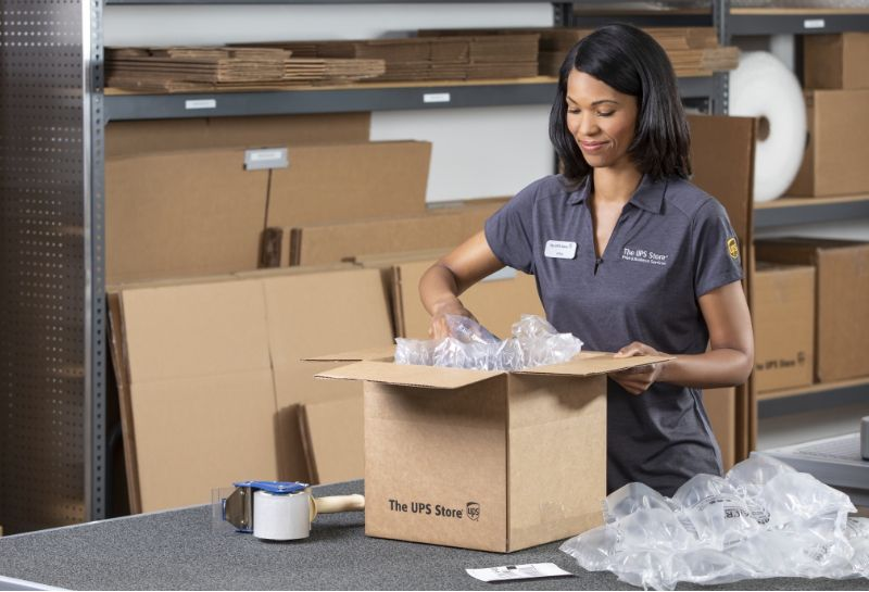 a woman packing a box at The UPS Store