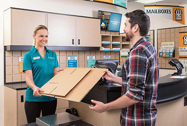 The UPS Store employee helping customer with box